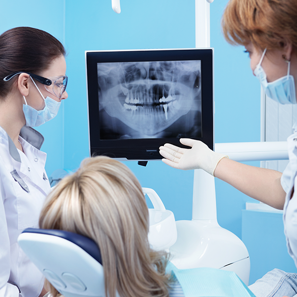 Dental assistant showing patient digital x-ray